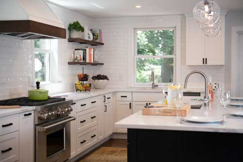 kitchen with white subway tiled walls and white stock cabinets that look custom