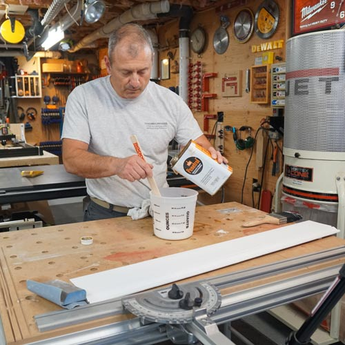 man adding paint conditioner to oil based paint to help eliminate brush strokes