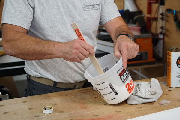 man mixing in paint conditioner to paint to help eliminate brush strokes and streaks