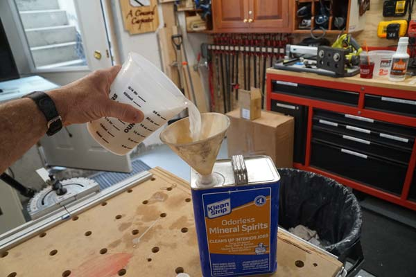recycling mineral spirits by pouring leftover paint thinner back into bottle for later use