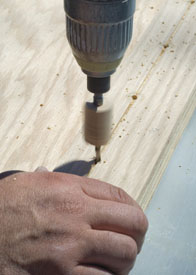A shallow kerf cut on the drill jig helped line up the layout for the adjustable shelves.