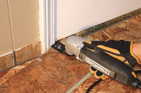 An oscillating tool like the Rockwell SoniCrafter makes quick work of undercutting door jambs to allow clearance for the new floor.
