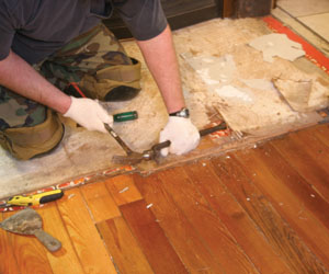 In the job shown, a double layer of 1/4-inch plywood and two vinyl floor coverings existed. The top vinyl and plywood layers were first removed.