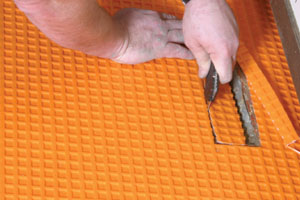 Schluter DITRA is rolled in place and cut to fit with scissors or a sharp knife.