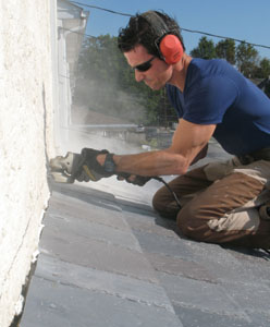 I kerf the stucco, install flashing bent on my sheet metal brake to trap the top course of shingles, and then seal with caulk.