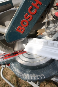 When cutting the corners, position the moulding against the miter saw fence upside-down and facing upward.