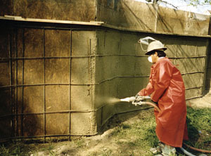 A man is applying the shotcrete for the concrete fence