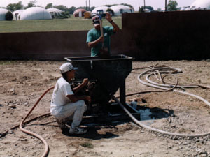 A portable concrete mixer, a concrete pump, a shotcrete gun, and hoses all being demonstrated in use